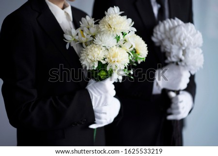 Mourning man and woman with flowers at funeral