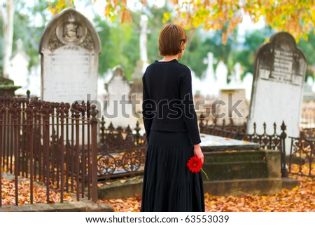 Mourning Woman at Cemetery with Red Flower