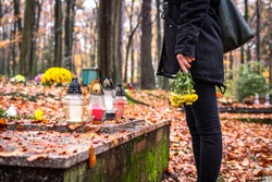Mourning woman holding flowers in hands and standing at grave in cemetery. Woman wearing black clothing at graveyard