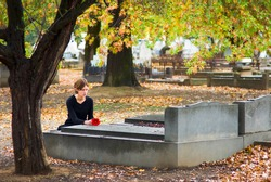 Mourning Woman Laying Flower on Grave in Cemetery in Fall