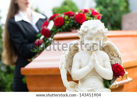 Mourning woman on funeral with red rose standing at casket or coffin