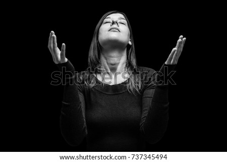 Mourning woman praying, with arms outstretched in worship to god, head up and eyes closed in suffer, on black background. Concept for religion, faith, prayer, grief, mourn, pain, depression.
