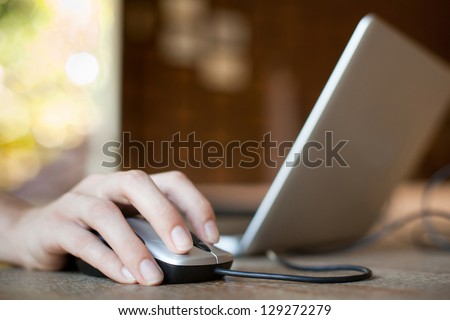 Photo of  mouse click, woman hand with mouse and laptop