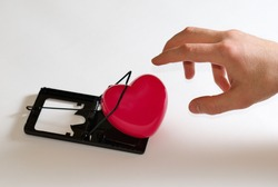 Mousetrap, heart, hand. Conceptual photography. Love trap. Heart trap