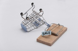 Mousetrap with sale bait and shopping trolley on white background. Trap or deception concept