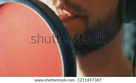 Mouth of male singer singing in sound studio. Unrecognizable man recording new song. Guy with beard sings to microphone. Working of creative musician. Show business concept. Slow motion Close up. #1211497387