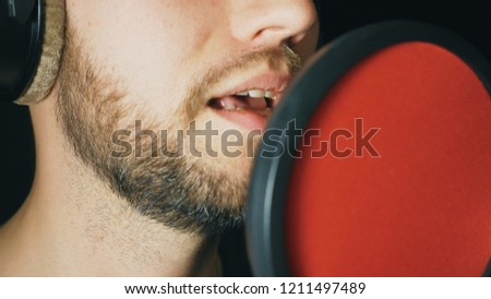 Mouth of male singer singing in sound studio. Unrecognizable man recording new song. Guy with beard sings to microphone. Working of creative musician. Dark background. Slow motion Close up. #1211497489