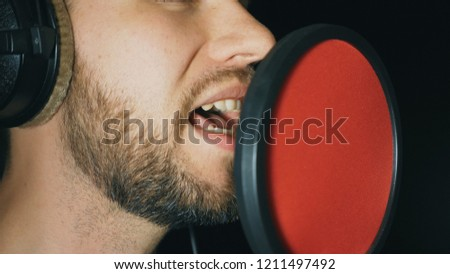 Mouth of male singer singing in sound studio. Unrecognizable man recording new song. Guy with beard sings to microphone. Working of creative musician. Dark background. Slow motion Close up. #1211497492