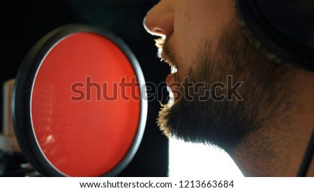 Mouth of male singer singing in sound studio. Unrecognizable man recording new song. Guy with beard sings to microphone. Working of creative musician. Show business concept. Slow motion Close up. #1213663684