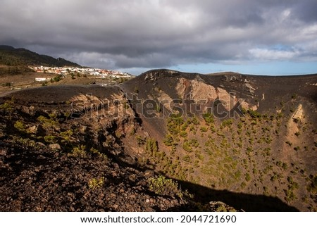 Mouth of one of the volcanoes, with lava and pine trees inside and behind a town, before eruption in Cumbre Vieja Natural Park, Canary Islands, Spain Foto stock ©