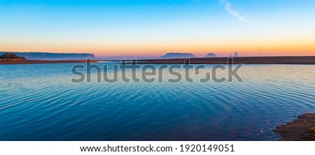 Mouth of the river Ter in the Mediterranean Sea with the Medes Islands and Estartit in the background. Panoramic sunrise landscape with the river flowing calmly. Morning lights with calm atmosphere. Stock fotó ©