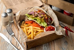 Mouth Watering big portion of gyros with shredded meat, vegetables and fries, appetizing photo for a magazine