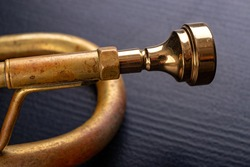 Mouthpiece of an old trumpet covered with patina. Musical instrument shown in magnification. Dark background.