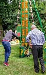 Movement is blurred as a man swings the hammer with enough force to ring the bell at the top. A 'high striker', 'strength tester', or strongman game is a typical english fairground attraction.