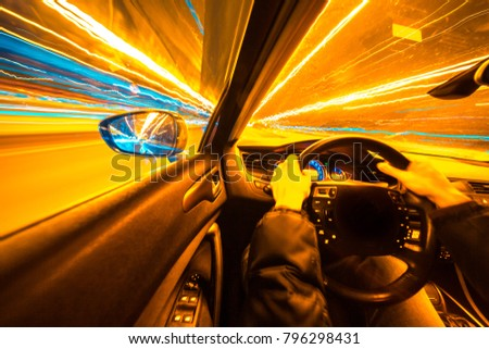 Movement of the car at night at high speed view from the interior with driver hands on wheel. Concept speed of life.