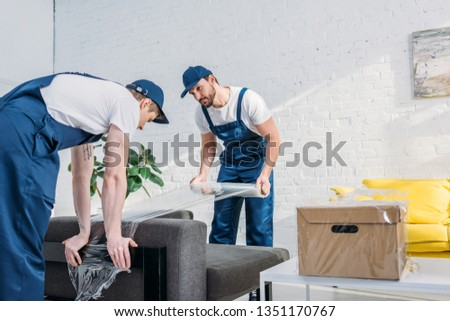 movers wrapping couch with roll of stretch film in apartment with copy space #1351170767