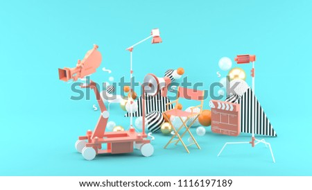 Movie camera, director chair,megaphone and movie clapper among colorful balls on a blue background.-3d rendering.