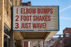 Movie cinema billboard with three rules to replace handshakes with elbow bumps, footshakes or just waving to friend during coronavirus epidemic