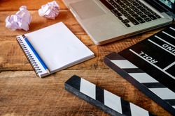 Movie clapper with notepad and pencil on wooden table