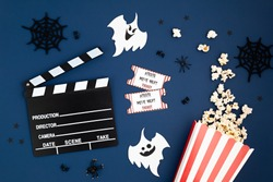 Movie clapperboard and halloween decoration. Horror movie night, halloween party invitation. Top view, copy space, mockup