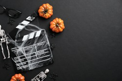 Movie clapperboard and halloween decoration on black table. Horror movie night, halloween party invitation. Halloween background