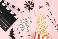 Movie clapperboard and halloween decoration over pink background. Horror movie night, halloween party invitation. Top view, copy space, mockup