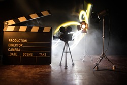 Movie concept. Miniature movie set on dark toned background with fog and empty space. Silhouette of vintage camera on tripod and clapboard. Selective focus