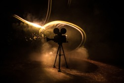 Movie concept. Miniature movie set on dark toned background with fog and empty space. Silhouette of vintage camera on tripod. Selective focus