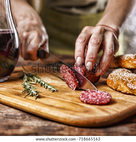 movie effect. Traditional Italian red wine, salami, rosemary, bread. Close up of a person's hand cut salami on a kitchen board.