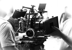 Movie shooting or video filming production by crew team and professional equipment such as super ultra high definition digital camera with tripod and lighting set in studio and black and white styles.