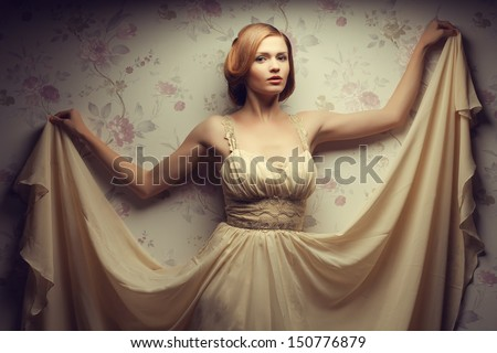 Movie star concept. Vintage portrait of a happy glamorous red-haired (ginger) girl posing in great flying beige dress and dancing. Retro (old Hollywood) style. Studio shot