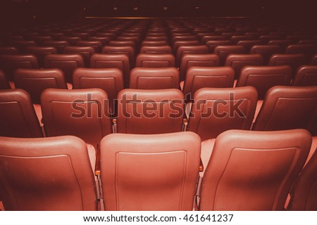 Movie theatre seats in red colors in a dark room #461641237