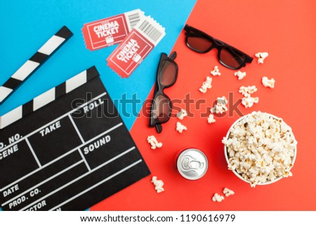 Movie time, flat lay. Cinema minimal concept. Composition on a red-blue background with a movie, popcorn, soda, 3D glasses and movie tickets #1190616979