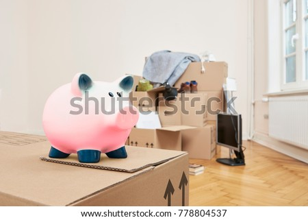 Moving - At the front left is a moving box on which a pink piggy bank stands. In the back part of the room is a stack of packed moving boxes
