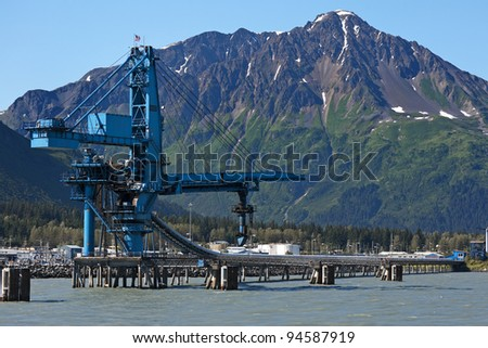 Moving belt and crane contraption in blue against green brown mountain under blue sky. - stock photo