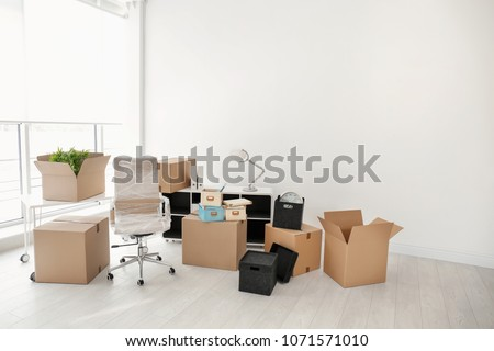 Moving boxes and furniture in new office #1071571010