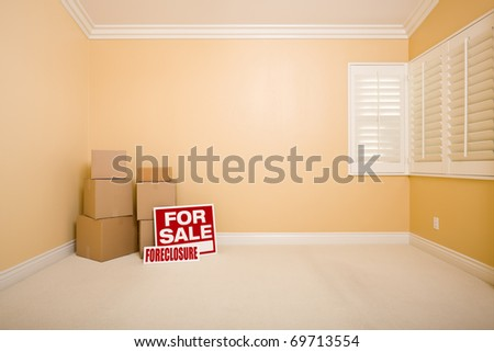 Moving Boxes, For Sale and Foreclosure Real Estate Signs on Floor in Empty Room with Copy Space on Blank Wall.