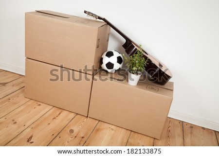 moving boxes, guitar and football in room