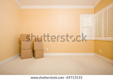 Moving Boxes in Empty Room with Copy Space on Blank Wall. - stock photo