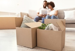 Moving Boxes Standing On Floor While Happy Black Couple Using Digital Tablet Packing For A House Move Sitting On Sofa Indoor. Family Housing, Real Estate, New Apartment Concept. Selective Focus