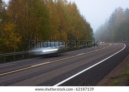 Moving cars on foggy weather in country road