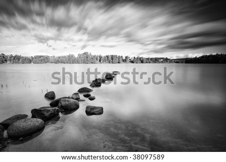 Moving clouds above a tranquil lake in black and white