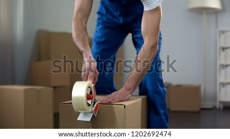 Moving company worker packing cardboard boxes, quality delivery services #1202692474