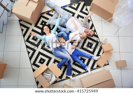 Moving concept. Happy family lying on carpet among cardboard boxes, top view