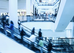 Moving crowd on escalator in modern interior