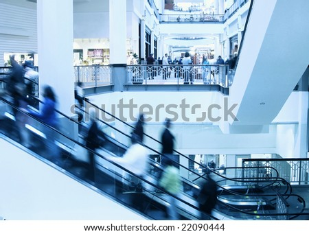Moving crowd on escalator in modern interior