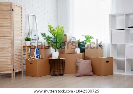 moving day and relocation concept - stack of cardboard boxes, houseplants and other domestic things in living room in new house Foto stock ©