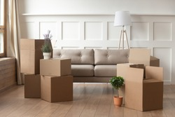 Moving day concept, cardboard carton boxes stack with household belongings in modern house living room, packed containers on floor in new home, relocation, renovation, removals and delivery service