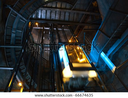 Moving elevator inside shaft with staircase.