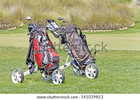 Moving golf bags around the green. Red and black zippered nylon bags and clubs mounted on a metal carrier with wheels.Easy to push and roll around golf course. Green bushes in the blurred background.